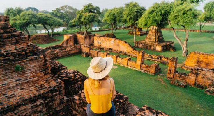 Young Caucasian woman sitting near the ruins of ancient Buddhist Temple, Ayutthaya, Thailand