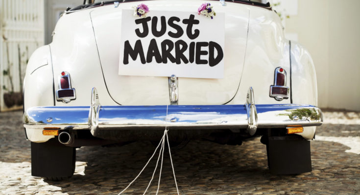 """Just Married"" sign and cans attached to convertible car's trunk. Horizontal shot."